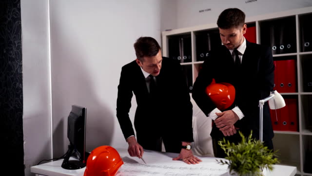 Two engineers businessmen look at architect drawing with helmet video