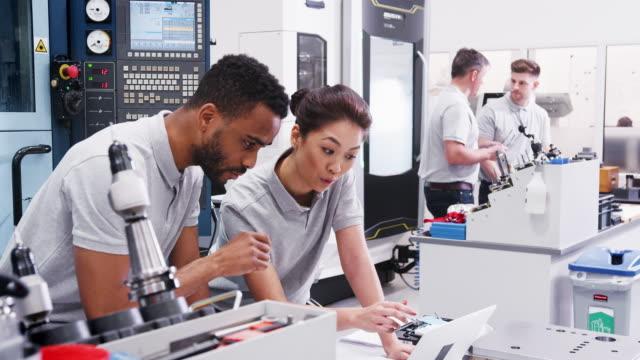 två ingenjörer diskutera planer för jobb samtidigt tittar på laptop - cnc maskin bildbanksvideor och videomaterial från bakom kulisserna