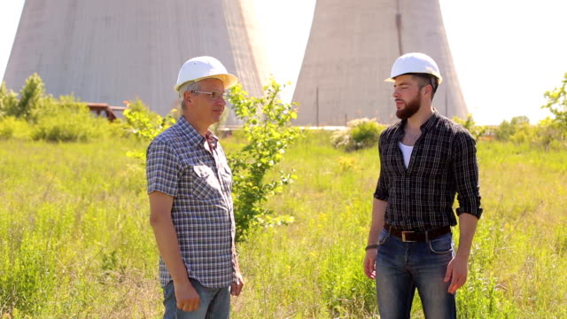 Two engineers in hard hats shaking hands. video