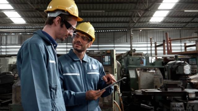 Deux ingénieurs en hardhat utilise une tablette numérique ensemble - Vidéo
