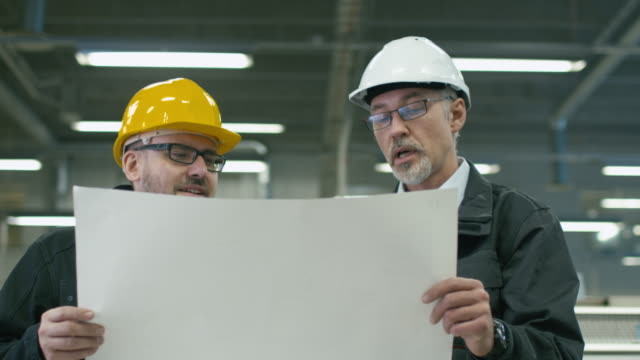 Two engineers in hardhats discuss a blueprint while standing in a factory. video