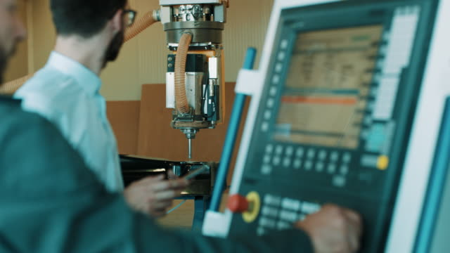 Two engineers is programming a CNC milling machine Two engineers is programming a CNC milling machine in factory production line worker stock videos & royalty-free footage