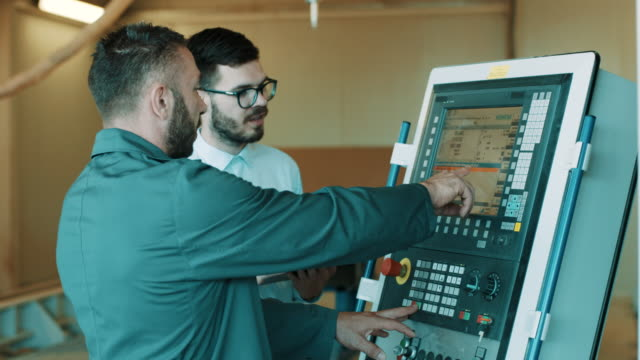 Two engineers is programming a CNC milling machine Two engineers is programming a CNC milling machine in factory computer aided manufacturing stock videos & royalty-free footage