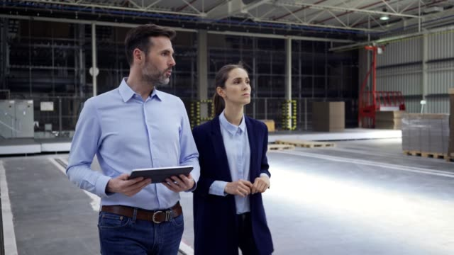 Two engineers looking at tablet and talking while walking in factory hall