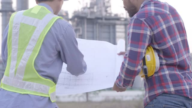 Two engineers male are looking at blueprint for workers security control at power plant. Energy power station area with sky, sunset. Concept safety,industry Two engineers male are looking at blueprint for workers security control at power plant. Energy power station area with sky, sunset. Concept safety,industry generation x stock videos & royalty-free footage