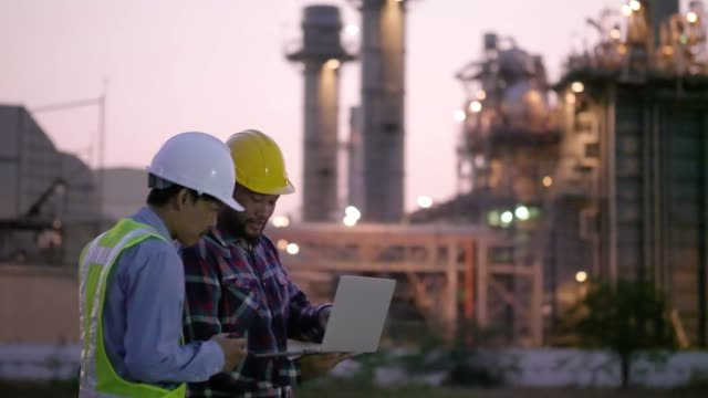 Two engineers male working with laptop and operate the radio for workers security control at power plant. Energy power station area During the twilight. Concept safety,industry