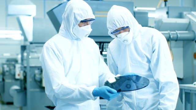 two engineers/ scientists/ technicians in sterile suits hold semiconductor silicon wafer that will be manufactured into computer chips. they work in a modern semiconductor manufacturing facility. - chip komputerowy filmów i materiałów b-roll