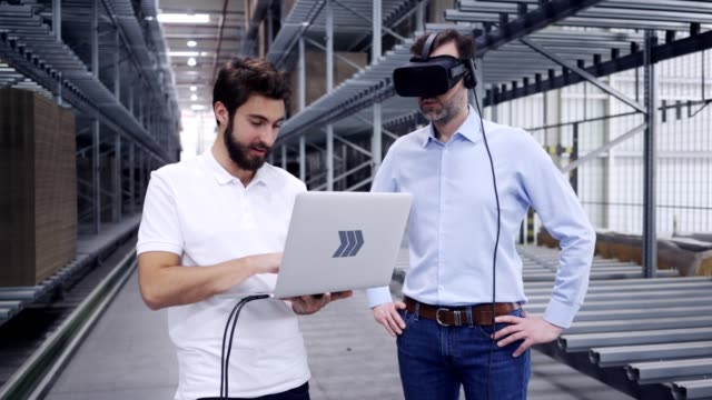 Two engineers testing virtual reality in factory warehouse with VR goggles and laptop