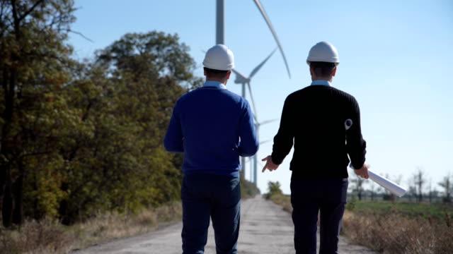 Two engineers walking towards wind farm