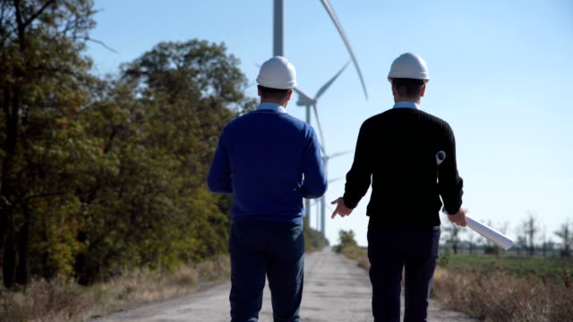 Two engineers walking towards wind farm Rear view of engineers walking along road towards wind farm with turbines on sunny day renewable energy stock videos & royalty-free footage
