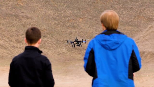 Two engineers watching the drone landing. Quadrocopters sits in automatic mode video