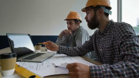 vidéos et rushes de deux ingénieurs travaillent ensemble dans le bureau - architecte