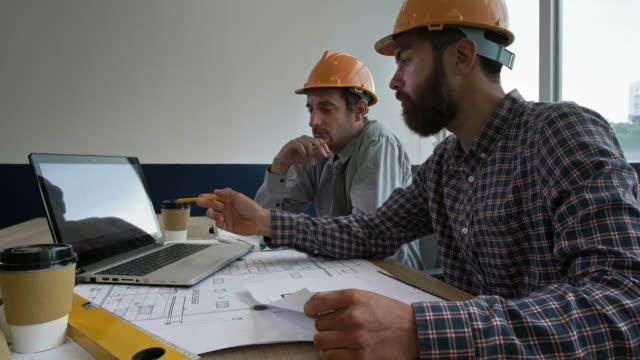 due ingegneri che lavorano insieme in ufficio - architetto video stock e b–roll