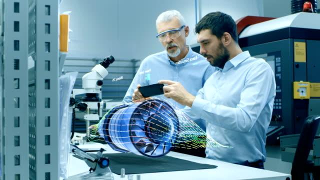 vídeos de stock, filmes e b-roll de duas obras de engenheiros com o uso de telefone móvel aumentaram realidade projeção holográfica 3d modelo de protótipo de turbina o motor. desenvolvimento de aplicação de realidade virtual mista. - holograma
