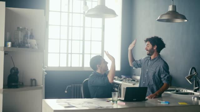 due dipendenti maschi entusiasti che si disfioiano in ufficio (slow motion) - america latina video stock e b–roll