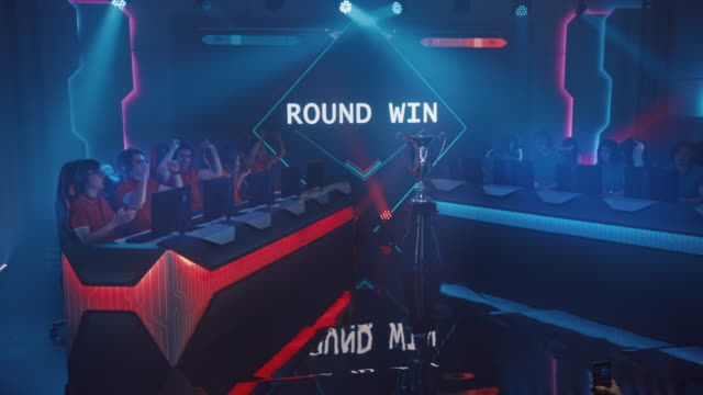 two esport teams of pro gamers play in fps shooter video game on a championship arena, team wins round and celebrates with high-fives.big screen showing mock-up gameplay. cyber games tournament event - współzawodnictwo wydarzenia filmów i materiałów b-roll