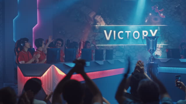 two esport teams of pro gamers play in rpg strategy video game on a championship arena, happy red team wins round and celebrates with high-fives.big screen showing mock-up gameplay. cyber games event - współzawodnictwo wydarzenia filmów i materiałów b-roll