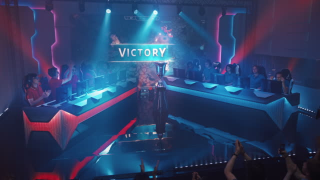 two esport teams of pro gamers play in rpg strategy video game on a championship arena, team wins round and celebrates with high-fives.big screen showing mock-up gameplay. cyber games tournament event - campionato video stock e b–roll