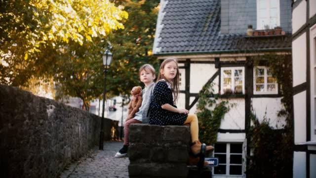 stockvideo's en b-roll-footage met twee europese kinderen zitten samen rug aan rug. broer en zus hebben plezier op een zonnige dag. verschillende persoonlijkheden 4k - sober leven
