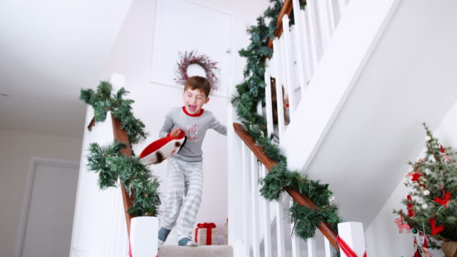Two Excited Children Wearing Pajamas Running Down Stairs Holding Stockings On Christmas Morning Excited brother and sister run down stairs at home on Christmas morning - shot in slow motion christmas stocking stock videos & royalty-free footage