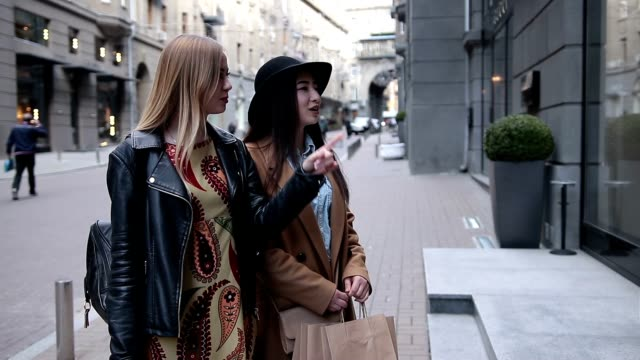 vídeos de stock, filmes e b-roll de dois animado elegantes mulheres olhando na janela da loja - boutique