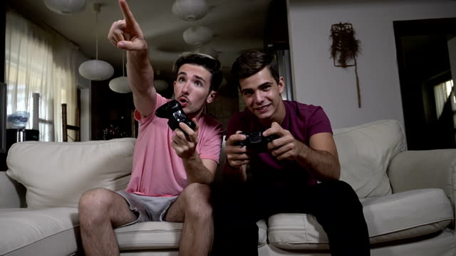vídeos de stock e filmes b-roll de two excited teen friends having fun playing tv games with wireless joysticks at home in slow motion - man joystick