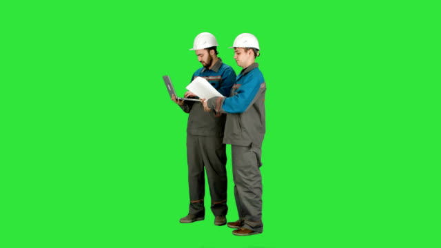 Two experienced industrial technicians work on laptop on a Green Screen, Chroma Key video