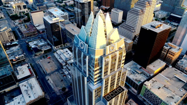 Two Faces of The Owl Tower or Frost Bank Tower aerial drone view pan right also called Owl Tower Austin Texas Sunrise Dramatic Colorful Morning video