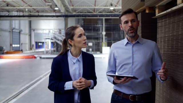 vidéos et rushes de deux directeurs d'étage d'usine discutant le travail tout en marchant et regardant la tablette - inspecteur