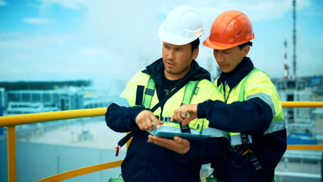 Two factory workers discussion with tablet pc. Industrial background Two factory workers discussion with tablet pc. Industrial background. gas pipe stock videos & royalty-free footage