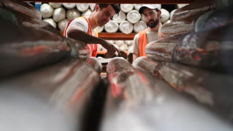 vídeos y material grabado en eventos de stock de dos trabajadores de la fábrica digital tablet quitar alfombra de estante - small business