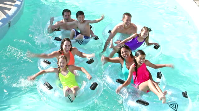 Two families on lazy river at water park Families and friends having fun at a water park, splashing each other as they float down the lazy river on inflatable rings. 30 39 years stock videos & royalty-free footage