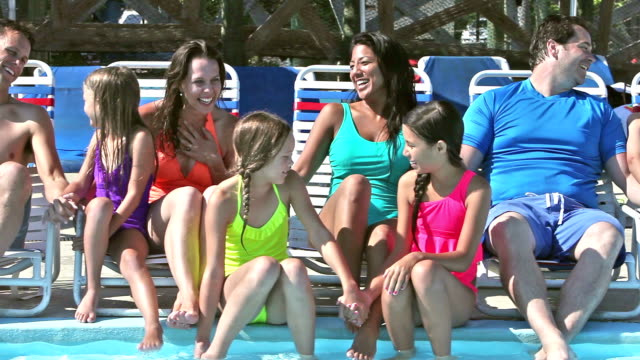 Two families sitting on lounge chairs by pool conversing video