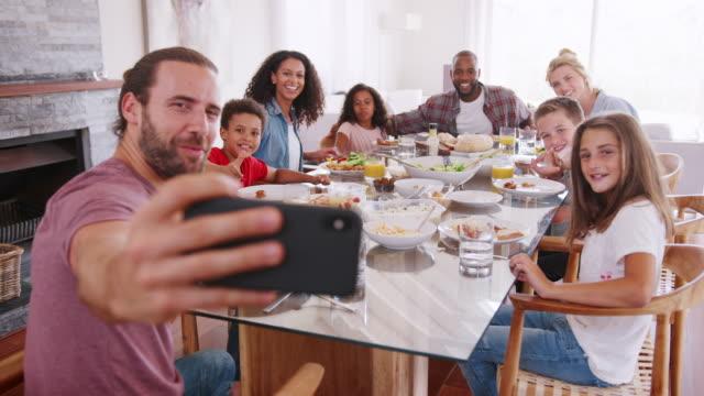 vídeos de stock, filmes e b-roll de duas famílias, tendo selfie como eles apreciam a refeição em casa juntos - almoço