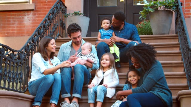 two families with kids sitting on front stoop in brooklyn - portico video stock e b–roll