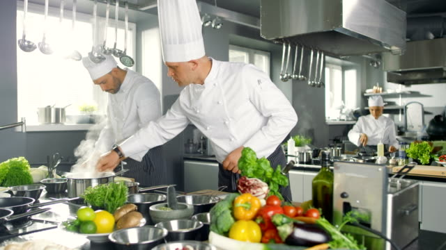Two Famous Chefs Work as a Team in a Big Restaurant Kitchen. Vegetables and Ingredients are Everywhere, Kitchen Looks Modern with Lots of Stainless Steel. video