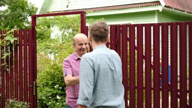stockvideo's en b-roll-footage met twee boeren schudden de handen en praten met elkaar op zonnige dag - buren