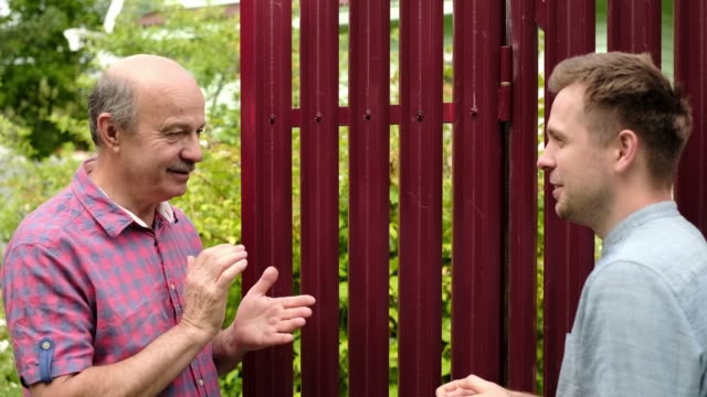 stockvideo's en b-roll-footage met twee boeren die op zonnige dag aan elkaar taklen. ze bespreken belangrijk nieuws - buren