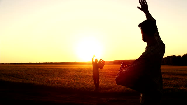 two farmers together carry a corn crop in a wooden box at sunset. - gospodarstwo ekologiczne filmów i materiałów b-roll