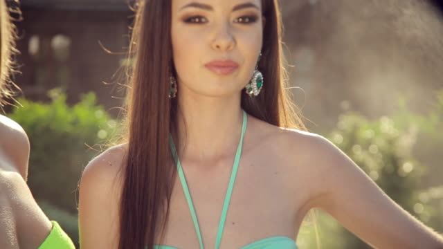 Two fashionable girls dressed in bikini and jewelry posing in the garden under splashes of water video