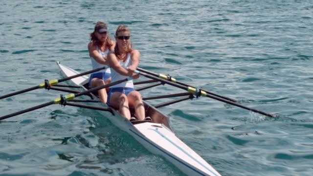 two female athletes in a double scull moving across the lake in sunshine - wiosłować ćwiczenie fizyczne filmów i materiałów b-roll