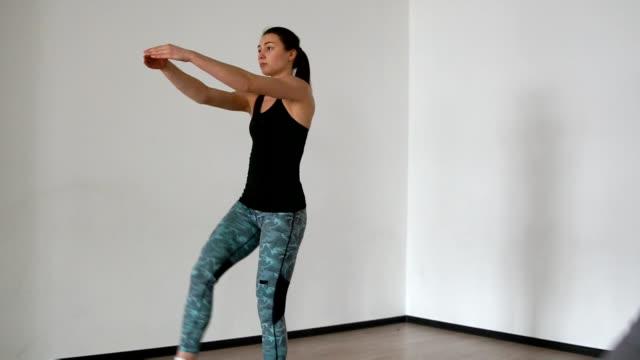 スポーツ ドレスの 2 つの女性アスリートは、自分の足のステップ アップを引き上げることを実行します。ストレッチと paletes は、個人レッスンでプロのインストラクターによって実行されます。クローズ アップ、カメラは一人の女の子から別に移動します。 - 人の筋肉点の映像素材/bロール