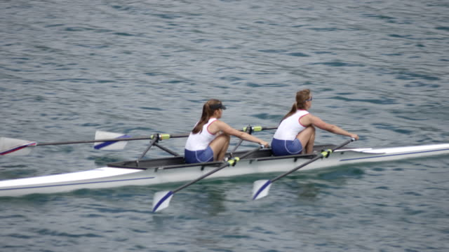 Two female athletes sculling across a lake video