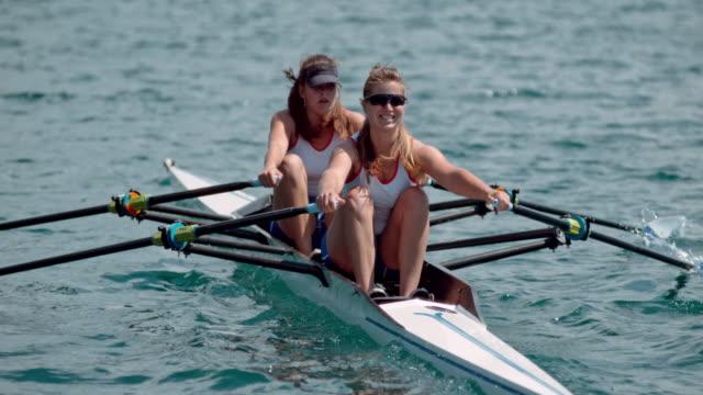 vídeos de stock, filmes e b-roll de slo mo dois atletas femininas lemada através do lago no sol - remo esporte aquático