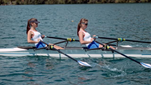 vídeos de stock, filmes e b-roll de slo mo ts duas atletas femininas lemada através do lago em um dia ensolarado - remo esporte aquático
