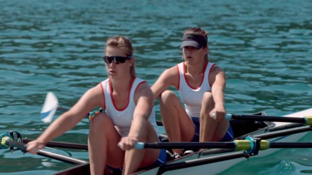 vídeos de stock, filmes e b-roll de dois atletas do sexo feminino lemada através da água no sol - remo atividade física