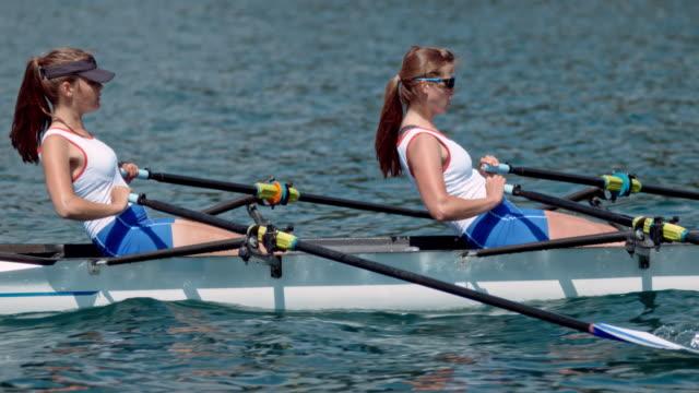 vídeos de stock, filmes e b-roll de slo mo ts duas atletas femininas lemada num lago ensolarado - remo esporte aquático