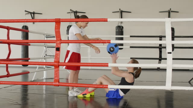 Two Female Boxers Doing Partner Sit Ups with Med Ball and Talking