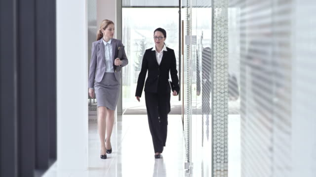SLO MO Two female business coworkers walking down hallway and talking video