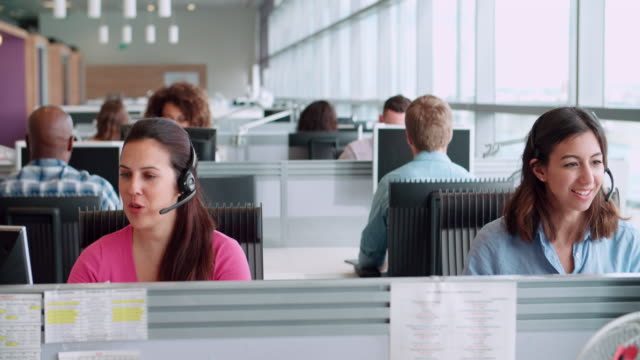 Two female call centre workers wearing headsets Two female call centre workers wearing headsets call centre videos stock videos & royalty-free footage
